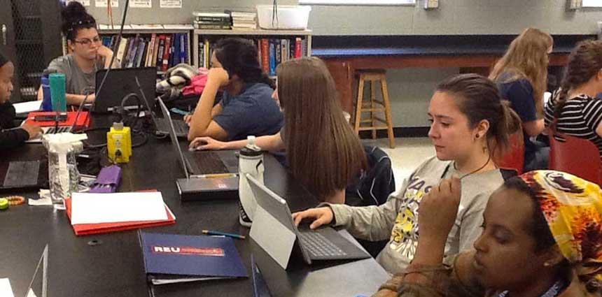 Students at desks looking at laptops in class